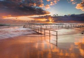 Обои закат, солнце, небо, облака, океан, берег, песок, волны, ограждение, забор, прилив
